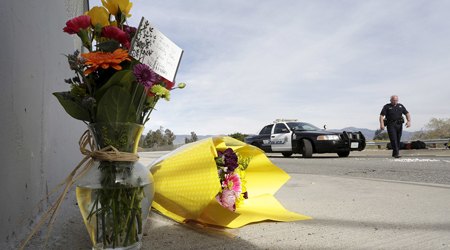 A San Bernardino police officer stands near flowers left near the scene of Wedneday's shooting rampage, at the Inland Regional Center, in San Bernardino, California December 3, 2015. © Jonathan Alcorn