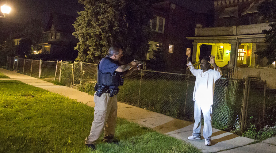 A Cook County Sheriff police officer (L) points his gun at a man who walked up to him while officers were conducting an unrelated street stop in the Austin neighborhood in Chicago, Illinois, United States, September 9, 2015. © Jim Young