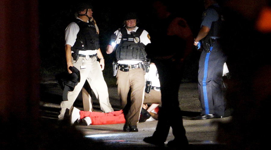 A black man lies badly wounded with blood on his shirt after a police officer-involved shooting in Ferguson, Missouri August 9, 2015. © Rick Wilking