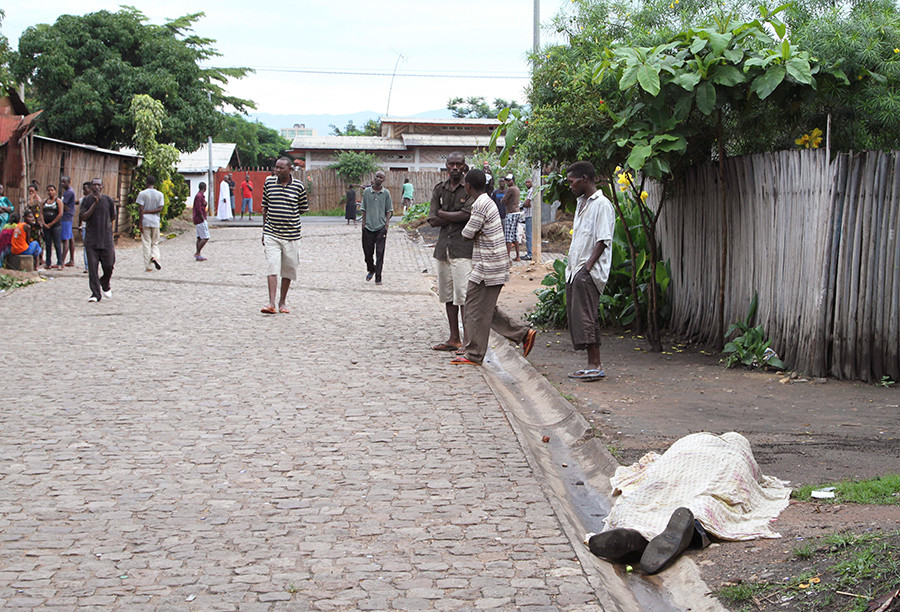 Residents look at the covered body of an unidentified man killed during gunfire, in the Nyakabiga neighbourhood of Burundi's capital Bujumbura, December 12, 2015 © Jean Pierre Aime Harerimana