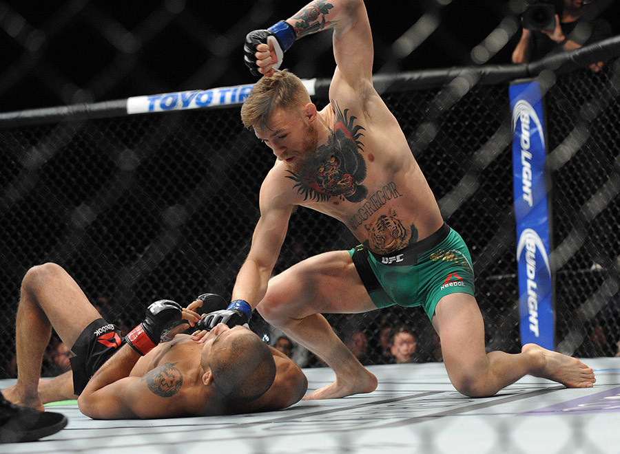 Conor McGregor lands punches to win b technical knockout  against Jose Aldo during UFC 194 at MGM Grand Garden Arena. © Gary A. Vasquez