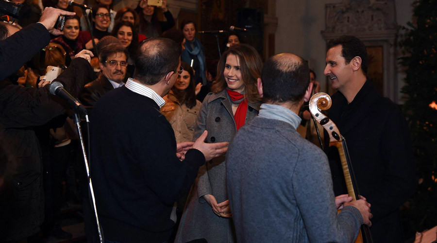 Syrian President Bashar Assad (R) and his wife Asma al-Assad (3rd-R) attending a Christmas choral presentation at the Lady of Damascus Catholic Church in the Syrian capital on December 18, 2015. © HO