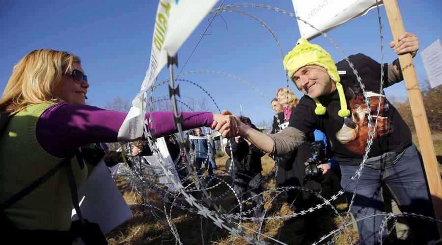 Women shake hands through razor wire during a protest against barbed wire fences along the border crossing between Slovenia and Croatia in Brezovica pri Gradinu, Slovenia December 19, 2015. © Srdjan Zivulovic