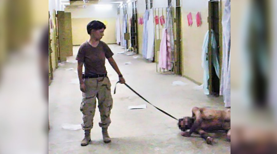 "Lynndie England holding a leash attached to a prisoner, known to the guards as ""Gus"" © Wikipedia"