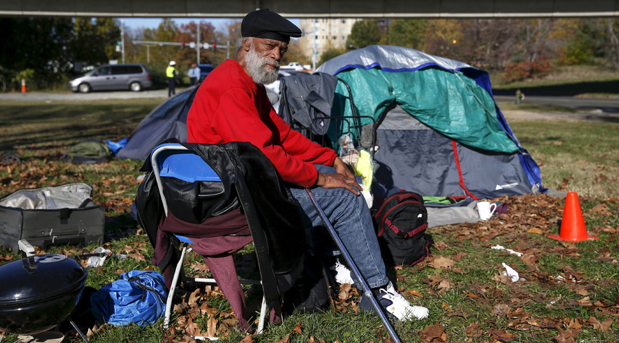 Owen Makel, 65, who has been homeless for nearly 14 years and has lived at the camp for four months, sits by his tent between the Watergate and Whitehurst Freeway in Washington D.C., November 16, 2015. © Shannon Stapleton