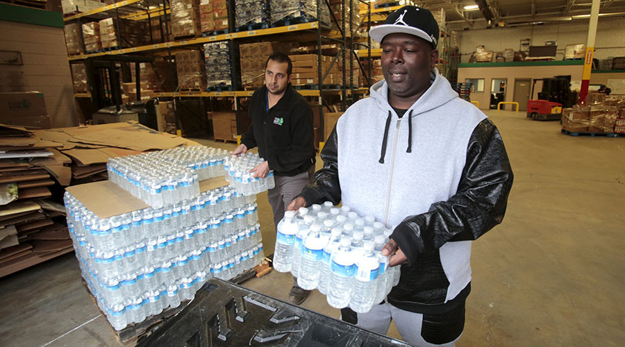 Man picks up bottled water from the Food Bank of Eastern Michigan to deliver to a school after elevated lead levels were found in the city's water in Flint, Michigan. © Rebecca Cook