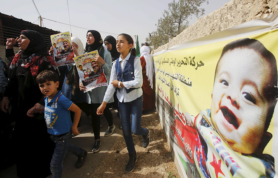 Mourners hold posters of Palestinian Riham Dawabsheh, 27 and her family as they walk past a banner depicting her 18-month-old son Ali during her funeral at Duma village near the occupied West Bank city of Nablus, September 7, 2015 © Abed Omar Qusini