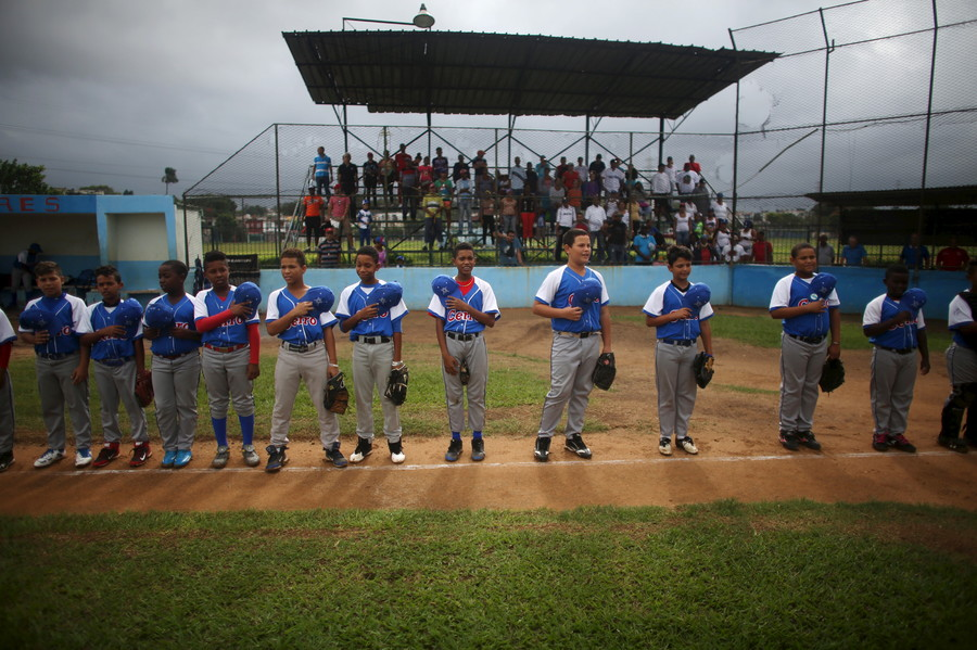 Players of the Cerro baseball team sing the national anthem before a game in Havana, December 19, 2015