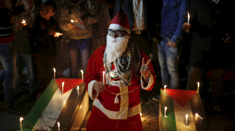 A Palestinian wearing a Santa Claus costume holds a candle during a rally to pay tribute to Palestinians who organizers said were killed recently by Israeli troops, on Christmas day in Gaza City December 25, 2015. © Suhaib Salem