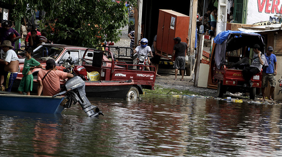 Paraguayans remove their belongings from their flooded houses near the Paraguay river in Asuncion. © Jorge Adorno