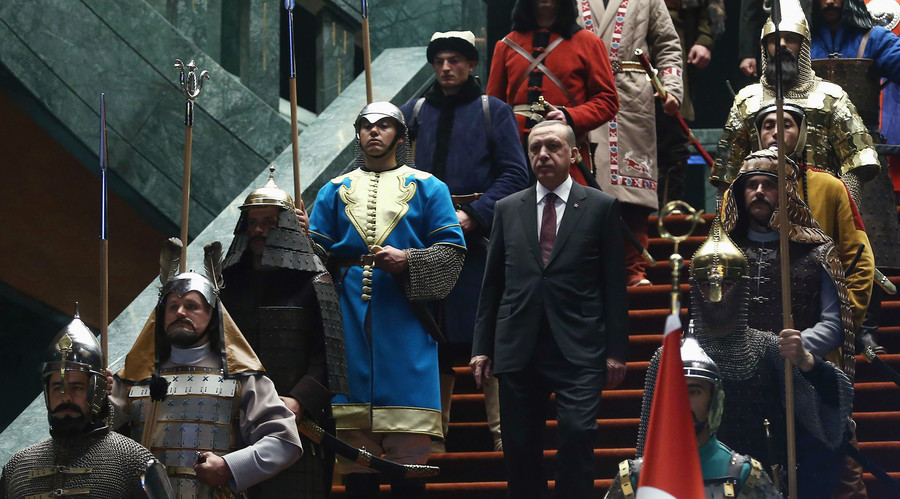 Turkey's President Tayyip Erdogan walks down the stairs in between soldiers, wearing traditional army uniforms from the Ottoman Empire. © Adem Altan