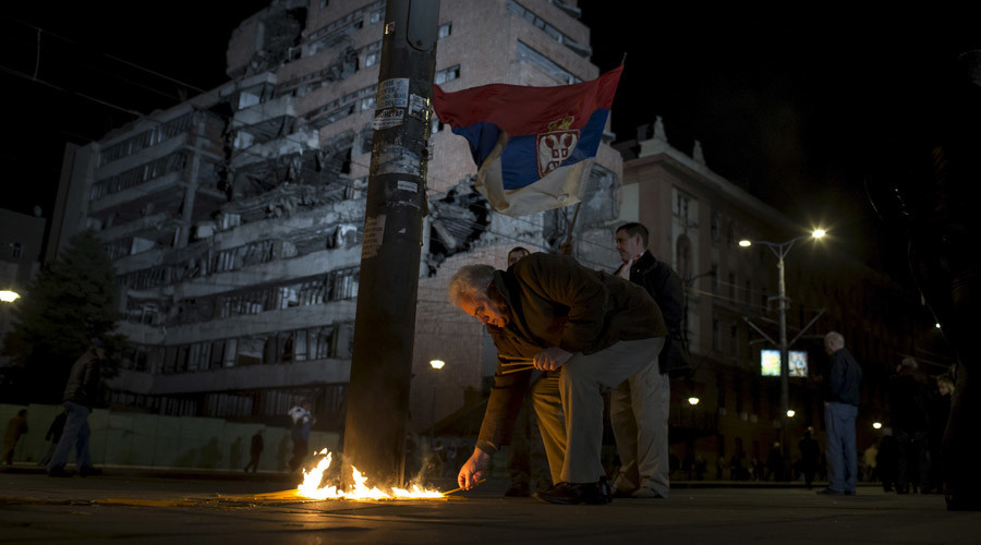 A man lights candles in front of a destroyed military headquaters as Serbia marks the 16th anniversary of the NATO bombing campaign in Belgrade © Marko Djurica
