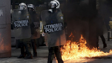 Greek riot police stand by fires caused by petrol bombs thrown by youths following brief clashes between police and protesters during a protest marking a 24-hour strike in Athens, Greece, December 3, 2015. © Alkis Konstantinidis