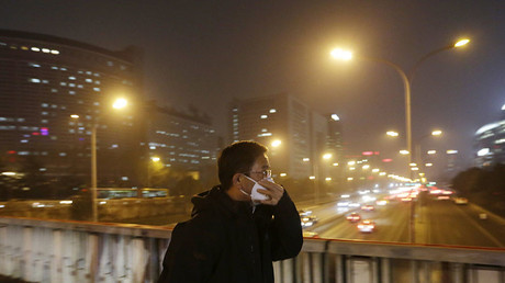 A man adjusts his protective mask amid the heavy smog in Beijing, China December 7, 2015. © Jason Lee
