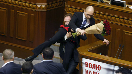 Rada deputy Oleg Barna removes Prime Minister Arseny Yatseniuk from the tribune, after presenting him a bouquet of roses, during the parliament session in Kiev, Ukraine, December 11, 2015. © Valentyn Ogirenko