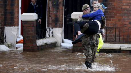A soldier carries a woman from a flooded house on a residential street in Carlisle, Britain, December 6, 2015. © Phil Noble