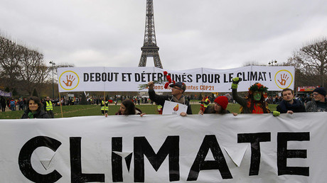 """Environmentalists hold a banner, reading """"Standing and Determined for the Climate"""" (Rear) at a protest near the Eiffel Tower in Paris as the World Climate Change Conference 2015 (COP21) continues near the French capital, December 12, 2015."""
