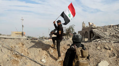 A member from the Iraqi security forces holds an Iraqi flag in the city of Ramadi © Reuters