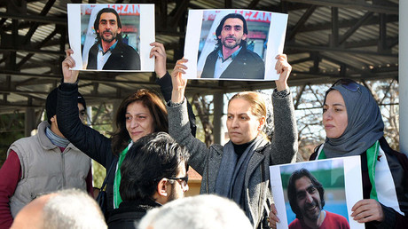 Women hold pictures of film maker Naji Jerf, who was killed on December 27, during his funeral in Gaziantep on December 28, 2015. © Stringer
