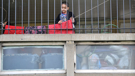 A child plays behind railings on the Robin Hood Gardens estate in Poplar, in East London © Jas Lehal