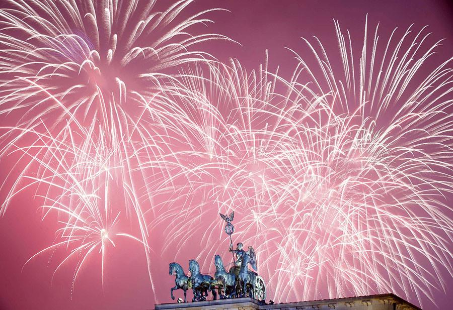 Fireworks explode next to the Quadriga sculpture atop the Brandenburg gate during New Year celebrations in Berlin January 1, 2016. ©Hannibal Hanschke