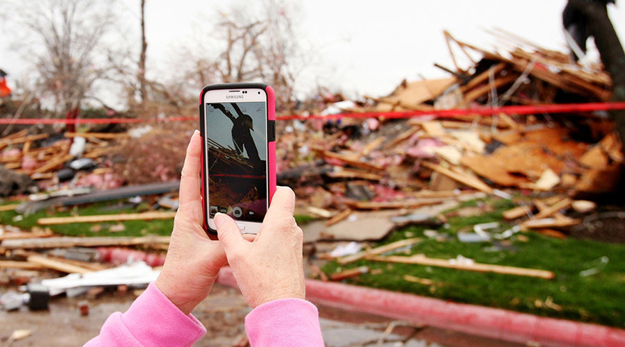 A former resident of the Landmark at the Lake Village West apartment complex takes photographs of tornado damage in Garland, Texas, December 28, 2015. © Todd Yates