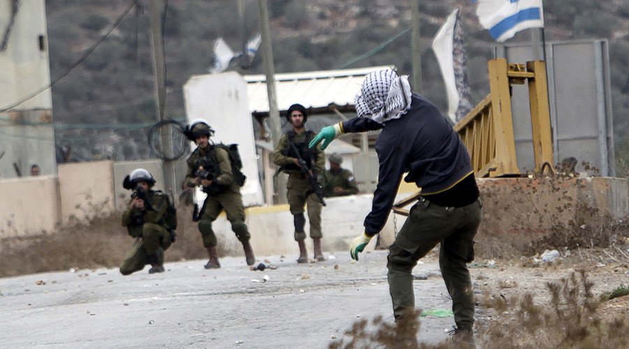 A Palestinian protester hurls stones towards Israeli soldiers © Mohammed Ballas