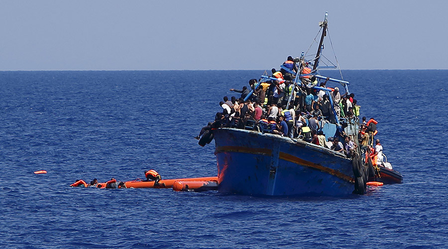 Migrants hang onto flotation tubes in the sea after jumping from an overloaded wooden boat during a rescue operation 16km off the coast of Libya August 6, 2015. © Darrin Zammit Lupi