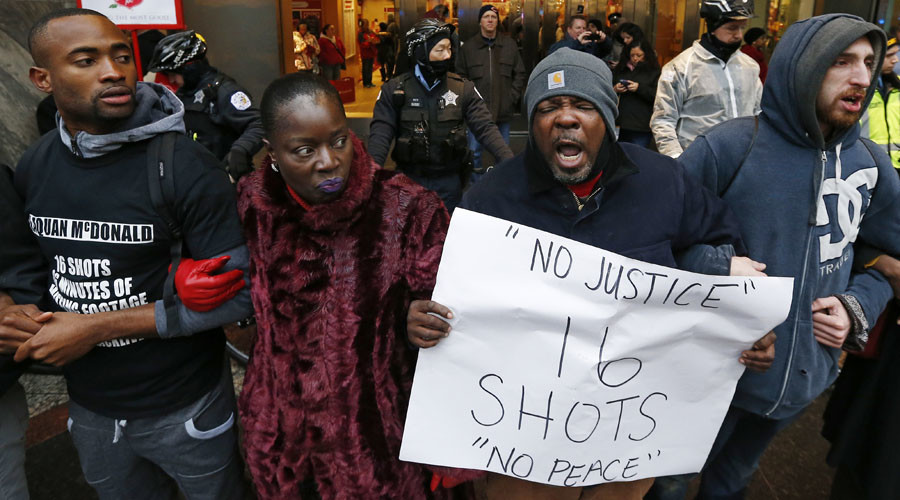 Demonstators link arms in solidarity as they protest last year's shooting death of black teenager Laquan McDonald by a white policeman and the city's handling of the case in the downtown shopping district of Chicago, Illinois © Jim Young