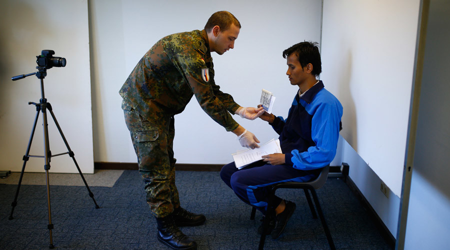 A German soldier (L) prepares a migrant prior to taking his identification photo  in Heidelberg, Germany © Ralph Orlowski