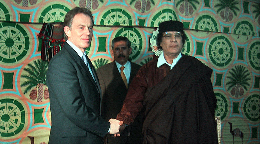 British Prime Minister Tony Blair (L) shakes hands with Libyan leader Muammar Gaddafi in a tent outside Tripoli, March 25. 2004. © Madeleine Chambers