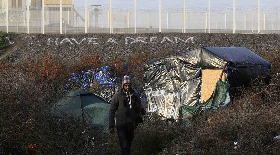 "A migrant walks between makeshift shelters near an embankment with the message, ""We Have A Dream"" below a fence topped with razor wire in the ""new jungle"", a field where migrants and asylum seekers gather in Calais, France, December 30, 2015. © Pascal Rossignol"