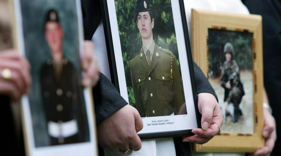 Family members hold portraits of their soldier relatives David James