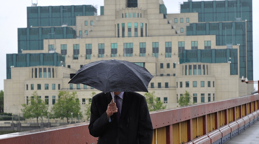 A man shields himself from the rain as he walks near the MI6 building in London. © Toby Melville