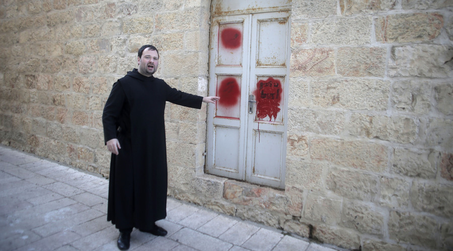 Father Nikodemus Schnabel spokesperson of the Dormition Abbey points towards anti-Christian graffiti in Hebrew, daubed on the Church of the Dormition, January 17, 2016. © Ahmad Gharabli