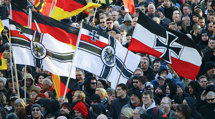 Supporters of anti-immigration right-wing movement PEGIDA carry various versions of the Imperial War Flag  during a demonstration march, in reaction to mass assaults on women on New Year's Eve, in Cologne, Germany January 9, 2016. © Wolfgang Rattay