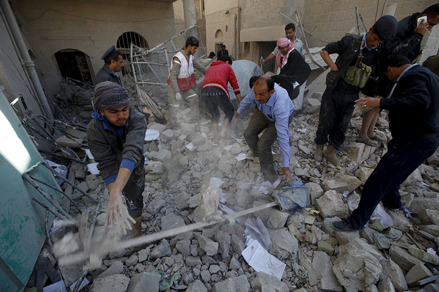 Policemen and medics remove debris as they search for victims at the site of a Saudi-led air strike on the police headquarters in Yemen's capital Sanaa, January 18, 2016. ©Khaled Abdullah