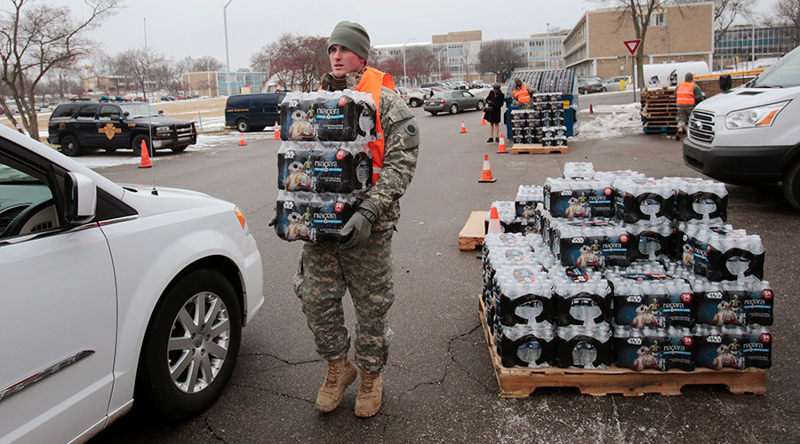 Michigan National Guard member Zach Burrell helps to distribute water to a line of residents in their cars in Flint, Michigan January 21, 2016 © Rebecca Cook