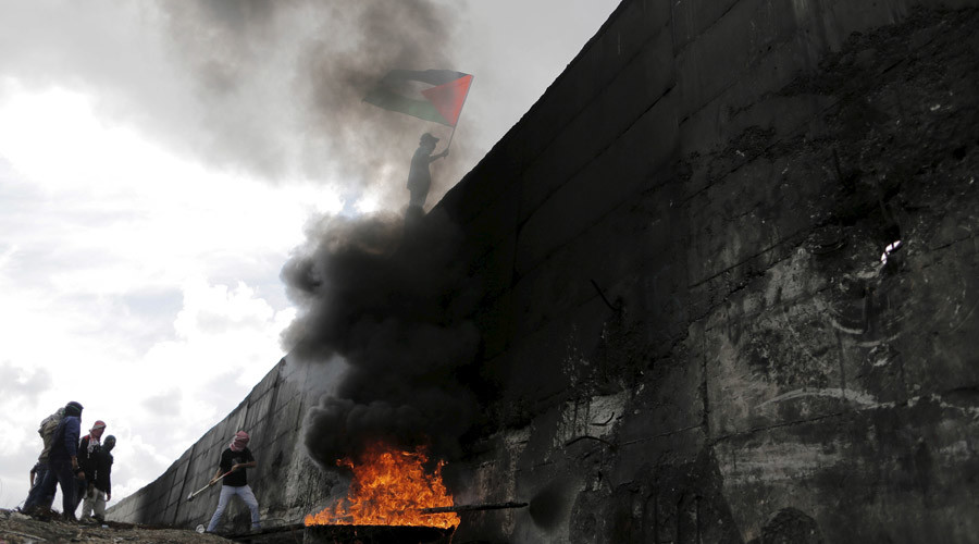 A Palestinian protester tries to hammer a hole through the Israeli barrier that separates the West Bank town of Abu Dis from Jerusalem, as another waves a Palestinian flag during clashes with Israeli troops © Ammar Awad