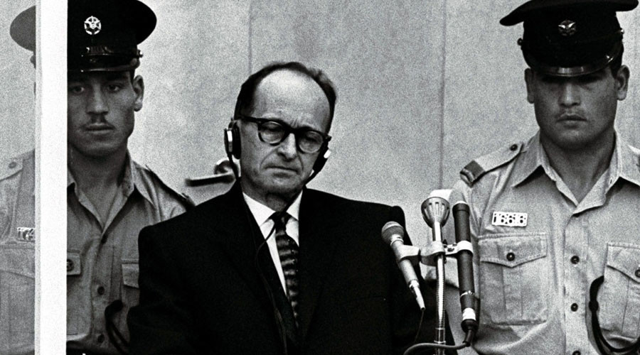 Israeli police flank Adolf Eichmann, the Nazi S.S. colonel who headed the Gestapo's Jewish Section and was responsible for millions of Jews' deaths in Nazi concentration camps, as he stands trial inside a bulletproof booth in a Jerusalem court. © AFP Photo
