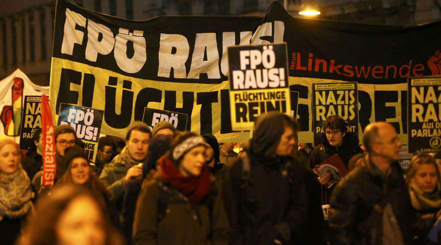 """Protesters march as they demonstrate against Austrian Freedom Party's (FPOe) Akademikerball ball in Vienna, Austria, January 29, 2016. The placards read, """"FPOe out - refugees in"""". © Leonhard Foeger"""