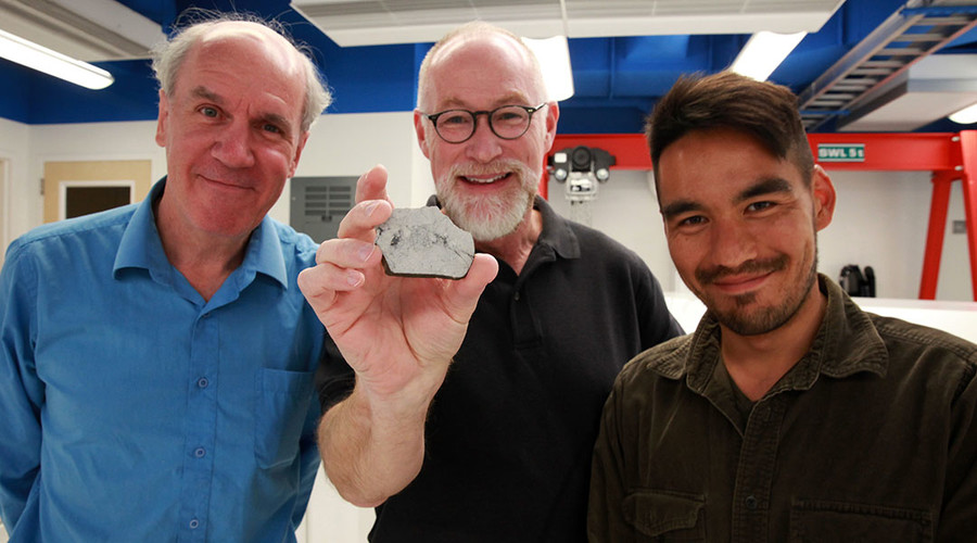(From left) Paul Warren, Edward Young and Issaku Kohl. Young is holding a sample of a rock from the moon. © newsroom.ucla.edu
