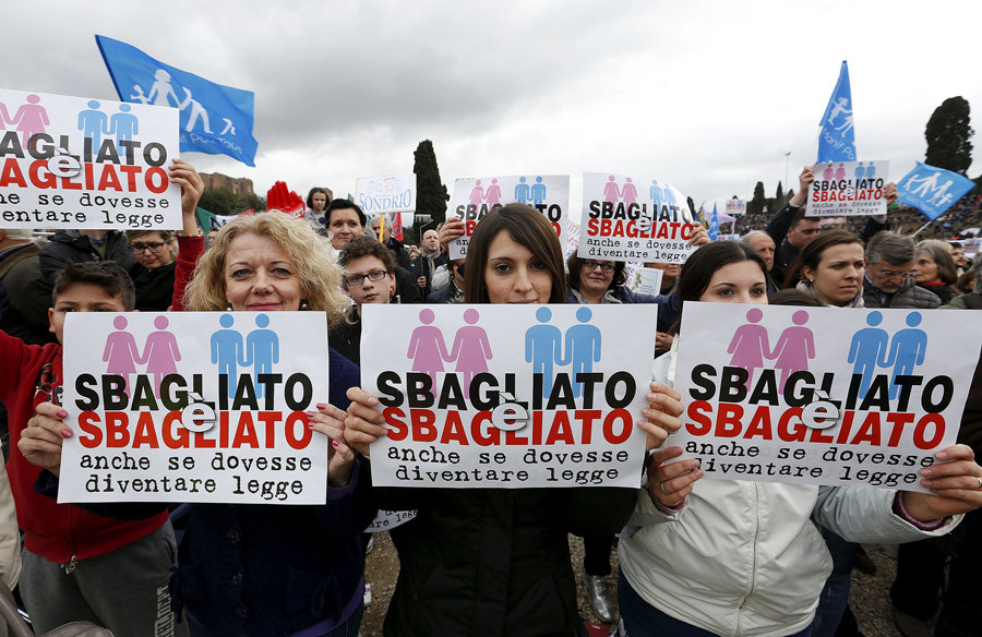 "Protesters hold signs reading ""It is wrong even if it becomes law"" during a rally against same-sex unions and gay adoption in Rome, Italy January 30, 2016.  © Remo Casilli"