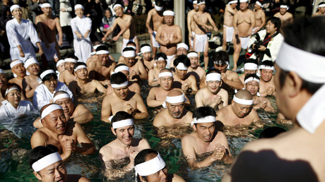"Men wearing the traditional ""fundoshi"" or loincloth pray as they bathe in ice-cold water at the Teppozu Inari shrine in Tokyo, Japan, January 10, 2016. © Yuya Shino"
