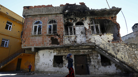 A woman walks past a damaged building in the southeastern town of Silvan in Diyarbakir province, Turkey, December 7, 2015. © Murad Sezer