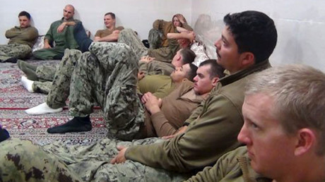 A photo released by Iran's Revolutionary Guard Corps shows US sailors sitting in an unknown place in Iran. © Reuters