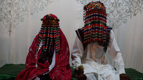 A bride and groom wearing traditional garlands, made of beads and cotton threads, on their foreheads, wait for their wedding to start during a mass marriage ceremony in Karachi © Akhtar Soomro