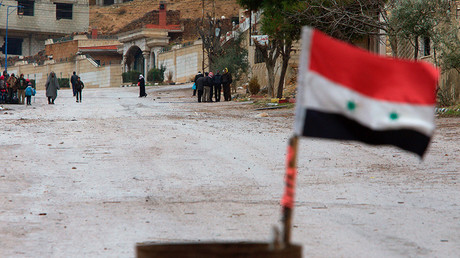 A Syrian national flag flutters near residents who said they have received permission from the Syrian government to leave the besieged town as they wait with their belongings after an aid convoy entered Madaya, Syria, January 14, 2016 © Omar Sanadiki