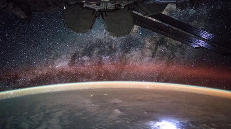 A large lightning strike on Earth lights up solar panels on the International Space Station. © NASA