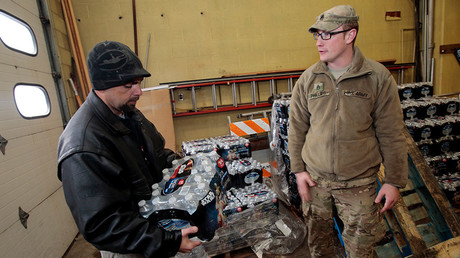 Michigan National Guard Staff Sergeant William Phillips (R) helps distribute bottled water to Flint residents at a fire station in Flint, Michigan © Rebecca Cook